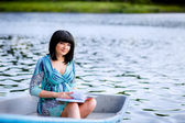 Beautiful pregnant girl in the boat — Stock Photo