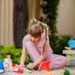 Stock Photo: Adorable little girl playing with toys in a sandbox