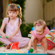 Two girls playing in a sandbox — Stock Photo