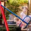 Happy children play on the swings — Stock Photo