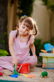 Adorable little girl playing with toys in a sandbox — Stock Photo