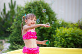 Happy girl splashing in the pool — Stock Photo