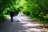 Bride and groom running down the alley — Stock Photo