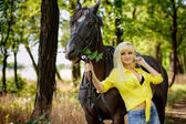 Beautiful girl on a walk with a horse — Stock Photo