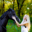 Beautiful young blonde woman sitting on a horse in white dress, in green garden. — Stock Photo