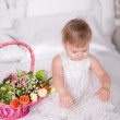 Girl in a beautiful dress on a bed with a basket of flowers — Stock Photo