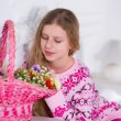 Girl on the bed with a basket of flowers — Stock Photo