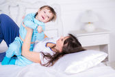 Happy Mom and son playing and laughing in their pajamas on the bed — Stock Photo