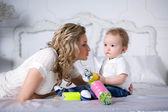 Mom with her son. Beautiful curly-haired boy with a big candy in the hands of — Stock Photo