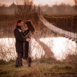 Young lovers near the rope bridge across the river — Stock Photo