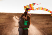 Happy young couple in love flying a kite — Stock Photo