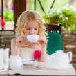 Blond girl drinking tea in the gazebo — Stock Photo