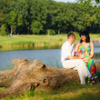 Pregnant woman with her husband  sitting on a tree — Stock Photo