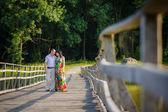 Pregnant woman with her husband on the bridge — Stock Photo