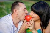Happy couple eating apple — Stock Photo