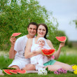 Happy family eating watermelon outdoors — Stock Photo