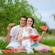 Stock Photo: Happy family eating watermelon outdoors