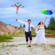 Wedding couple with an umbrella and flying kite — Stock Photo