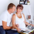 Beautiful pregnant woman with her husband looking pictures. — Stock Photo