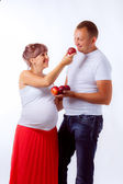Pregnant woman and her husband with peach — Stock Photo