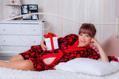 Pregnant woman on a bed with a gift — Stock Photo