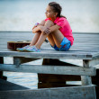 Girl sitting on a pier with a guitar — ストック写真