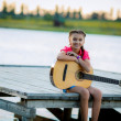 Girl playing a guitar near the river — Stock Photo