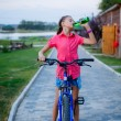Beautiful teenage girl drinks water after a bike ride — Stock Photo #29323943
