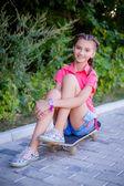 Beautiful teenage girl riding a skateboard — Stock fotografie