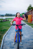 Beautiful teenage girl drinks water after a bike ride — Stock Photo