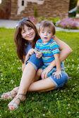 Madre con el niño en el césped — Foto de Stock