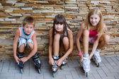 Três amigos usam patins — Fotografia Stock