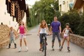 Moeder, vader en kinderen lopen, fietsen, skaten — Stockfoto