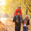 Young family in autumn park — Stock Photo