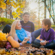 Young family having a picnic in the autumn park — Stock Photo