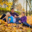Stock Photo: Young family having a picnic in the autumn park