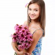 Girl happily sitting with a small bouquet. — Stock Photo