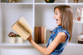 Girl in her room with a book — Stock Photo