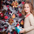 Girl near the Christmas tree with a gift. — Stock Photo