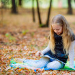 Girl in park reading a book — Stock Photo