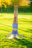 Blond girl standing on her head — Stock Photo