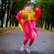 Happy girl in a raincoat walking through puddles — Stock Photo