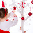 Little girl dresses up a fir-tree — Stock Photo