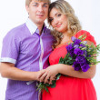 Stock Photo: Pregnant womwith her husband with bunch of flowers
