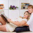 Pregnant woman with  husband reading magazine — Foto Stock