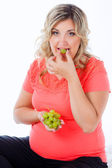 Beautiful pregnant girl eating grapes — 图库照片