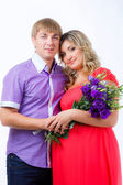 Pregnant woman with her husband with bunch of flowers — Stock Photo