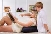 Pregnant woman with husband reading magazine — Stock Photo