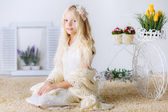 Girl sitting among the flowers and decorations — Stock Photo