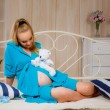 Pregnant woman  with booties and teddy bear — Stock Photo